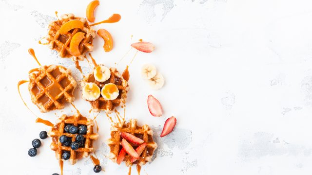 Traditional belgian waffles with fresh fruit and caramel. Flat lay, top view